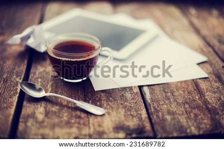 Digital tablet with note paper and cup of tea on old wooden desk. Simple workspace or coffee break in morning/ selective focus  #231689782
