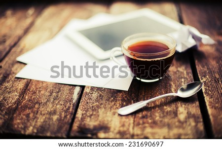Digital tablet with note paper and cup of tea on old wooden desk. Simple workspace or coffee break in morning/ selective focus  #231690697