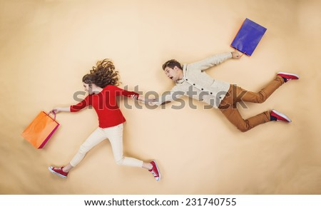 Young couple having fun running with shopping bags against the beige background #231740755