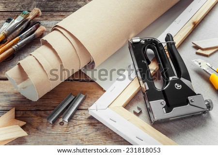 Artist canvas in roll, canvas stretcher, staple gun and paintbrushes on old table #231818053