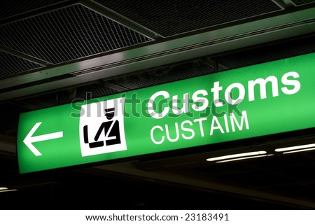 Customs sign in Airport and direction arrow, green and lighted.