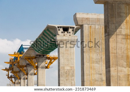 Construction of a mass transit train line in progress with heavy infrastructure.  This photo shows the progress in joining the various blocks/modules of the line with heavy equipment. Royalty-Free Stock Photo #231873469