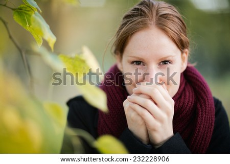 A young woman warms up her hands with her own breath as she looks at the camera. Photographed in a park in the Autumn or Fall. #232228906