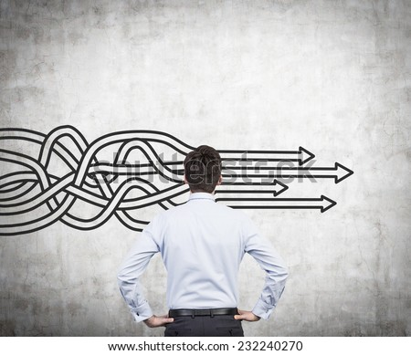 Businessman is standing in front of concrete wall with drawn arrows. Thinking about structuring business process and solutions. #232240270