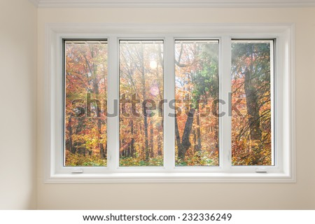 Large four pane window looking on colorful fall forest