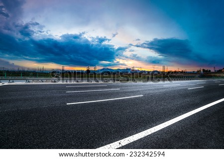 Asphalt road High way Empty curved road clouds and sky at sunset