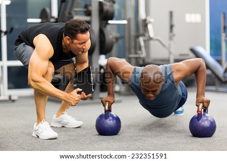 personal trainer motivates client doing push-ups in gym Royalty-Free Stock Photo #232351591