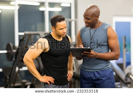 african personal trainer helping man to fill the membership form of health club Royalty-Free Stock Photo #232353118
