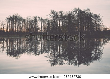 reflections in the lake water at sunrise. Vintage photography effect.