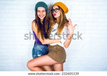 Studio lifestyle portrait of two best friends hipster girls wearing stylish bright outfits, hats, denim shorts and glasses, going crazy and having great time together. White urban wall background.