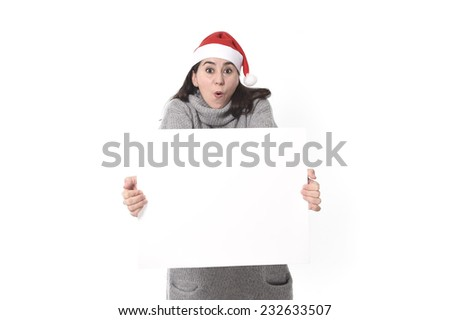 young attractive Hispanic woman wearing Santa Claus Christmas hat and winter jumper holding blank billboard or placard sign as copy space for adding text advertising isolated on white background #232633507