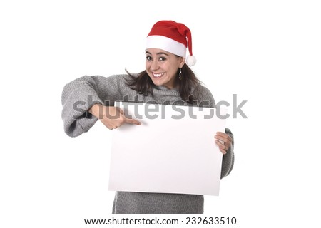 young attractive Hispanic woman wearing Santa Claus Christmas hat and winter jumper holding pointing blank billboard placard sign as copy space adding corporate marketing isolated on white background #232633510
