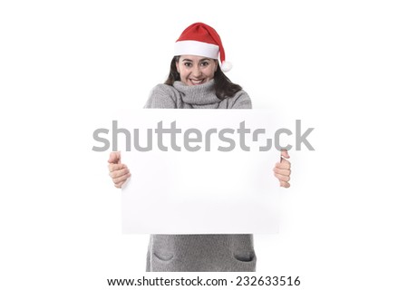 young attractive Hispanic woman wearing Santa Claus Christmas hat and winter jumper holding blank billboard or placard sign as copy space for adding text advertising isolated on white background #232633516