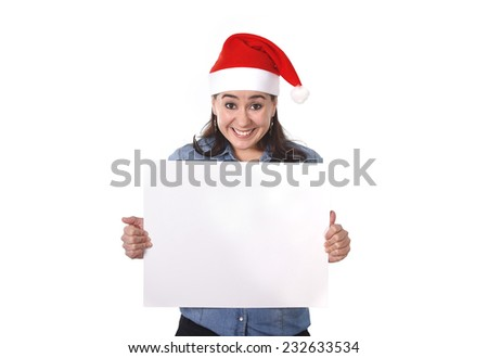 young attractive Hispanic woman wearing Santa Claus Christmas hat and blue shirt holding blank billboard or placard sign as copy space for adding corportate marketing isolated on white background #232633534