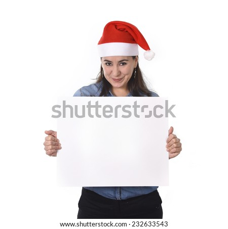 young attractive Hispanic woman wearing Santa Claus Christmas hat and blue shirt holding blank billboard or placard sign as copy space for adding corportate marketing isolated on white background #232633543