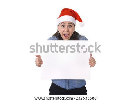 young attractive Hispanic woman wearing Santa Claus Christmas hat and blue shirt holding blank billboard or placard sign as copy space for adding corportate marketing isolated on white background #232633588
