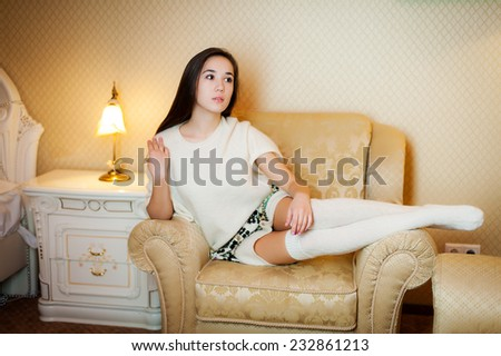 Woman near a bed in a light sweater #232861213