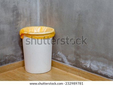 The white can bin at the corner on wooden floor with exposed cement background, for cleaning and recycle. #232989781