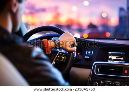 Driving a car at night -man driving his modern car at night in a city (shallow DOF; color toned image) Royalty-Free Stock Photo #233041750