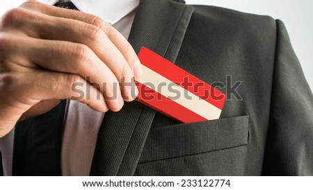 Man withdrawing a wooden card painted as the Austrian flag from his suit pocket, close up of his hand. #233122774
