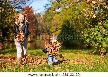 Little boy and mother playing together in the autumn park #233133130