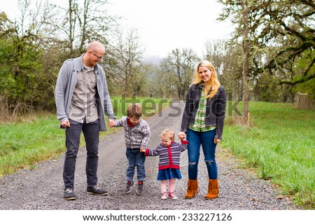 Family photo of a mother, father, and their two kids a boy and girl outdoors in the Fall.