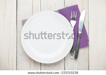 Empty plate and silverware over white wooden table background. View from above #233310238