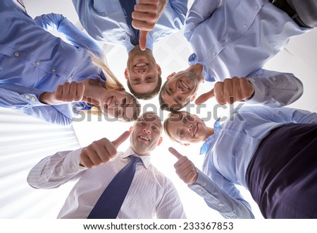 business, people and teamwork concept - smiling group of businesspeople standing in circle and showing thumbs up gesture #233367853