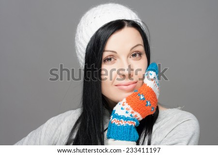 Winter Beauty Woman. Fashion Girl Concept. Skin and hair care in cold season. Beautiful woman with long hair wearing a sweater, scarf, hat and gloves. #233411197