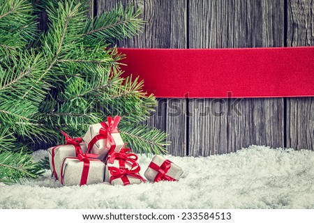 Christmas background with small gifts, red ribbon and spruce branch
