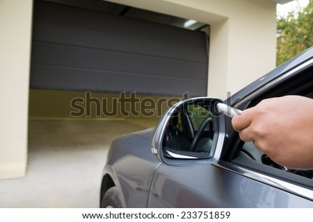 driver opens the garage with remote control from the comfort of a car Royalty-Free Stock Photo #233751859