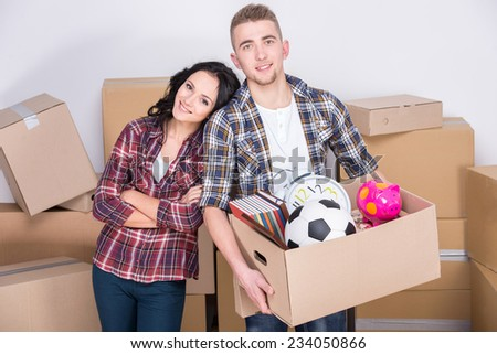 Happy couple are carrying cardboard moving boxes in their new home. #234050866