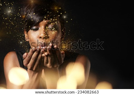 beauty woman blowing golden dust to the camera. Make a wish concept. Flair #234082663