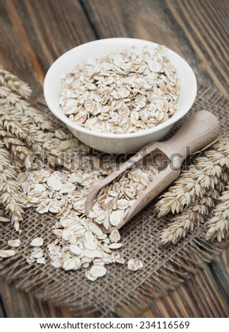 Bowl of oatmeal and wheat on dark wooden background #234116569
