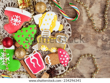 Homemade christmas painted gingerbreads on the wooden background with Christmas decorations. Selective focus and place for text. Toned