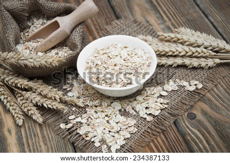 Bowl of oatmeal and wheat on dark wooden background #234387133