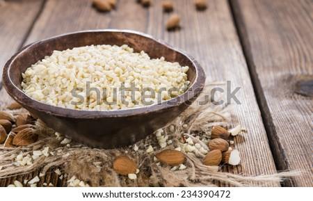 Minced Almonds (detailed close-up shot) on dark wooden background #234390472