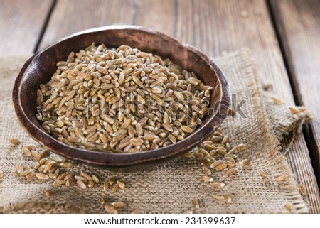 Heap of Spelt on dark wooden background (close-up shot) #234399637