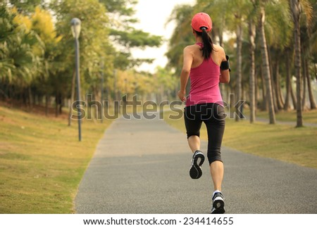 Runner athlete running at tropical park. woman fitness jogging workout wellness concept.  #234414655