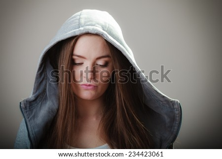 Portrait of young woman teen girl long hair  in hooded sweatshirt on gray background #234423061