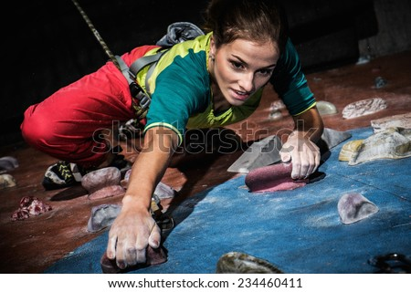 Young woman practicing rock-climbing on a rock wall indoors Royalty-Free Stock Photo #234460411