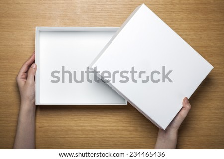 A female(woman) hands hold a empty(blank) white box on the desk(table) top view at the studio. #234465436
