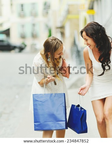 happy women with shopping bags walking downtown #234847852