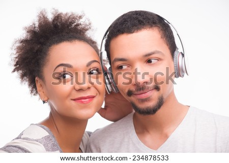 Half-length portrait of handsome smiling man standing in earphones near his smiling girlfriend also wanted to listen to music. Isolated on white background #234878533