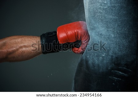 Hand  of boxer and punching bag over black background Royalty-Free Stock Photo #234954166
