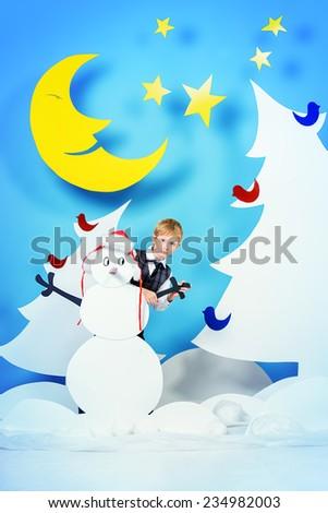 Cheerful boy in a cartoon fairy snowy forest. The magic of Christmas night. Full length portrait.
