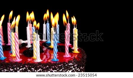 There is celebratory pie with burning candles on a black background. Cropped.