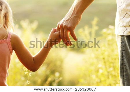 a parent holds the hand of a small child #235328089