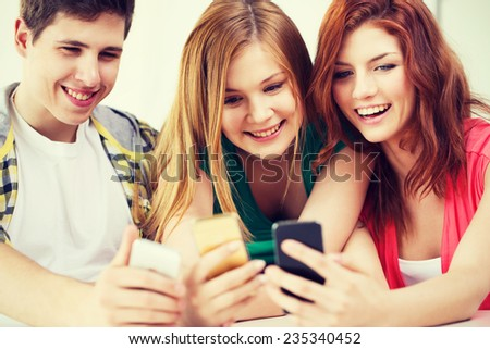 education, relationships and technology concept - three smiling students with smartphone at school Royalty-Free Stock Photo #235340452