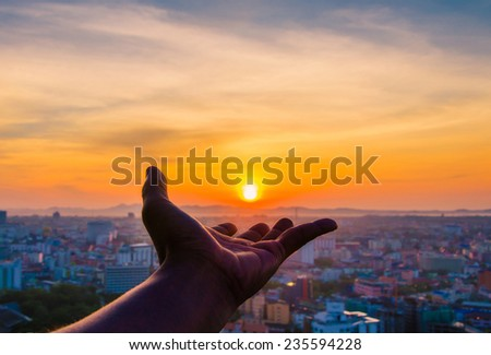 Hand holding sunset and city of background.